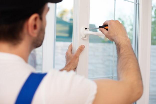 Young professional worker man in uniform suit is installing window with help of tools Premium Photo