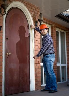 Молодой профессиональный работник измерения металлической двери с лентой