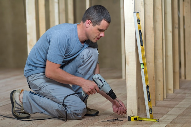 Young professional worker uses level and screwdriver installing wooden frame for future walls.