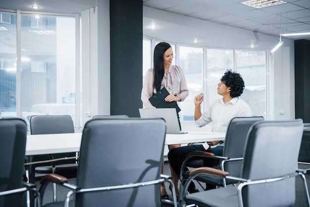 若い専門家。ラップトップを使用して仕事をしているときに笑みを浮かべて近代的なオフィスで陽気な同僚