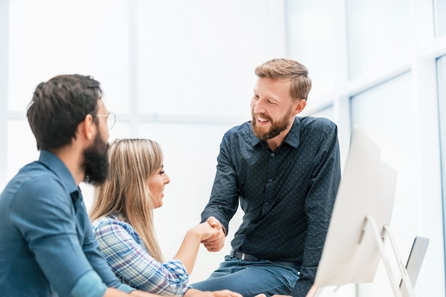 職場で握手する若い専門家。チームワークの概念