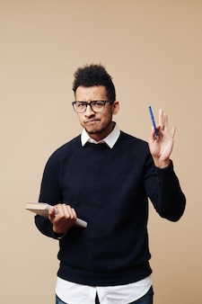 ベージュの壁に眼鏡をかけて説明しながら本を持っている若い教授