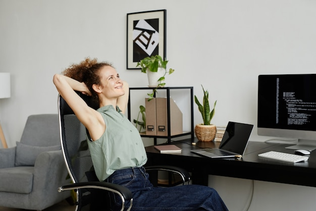 Young programmer sitting on comfortable chair and stretching she resting after hard with computers