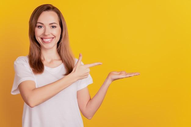 젊은 발기인 여성 직접적인 집게손가락 빈 공간은 노란 벽에 손바닥 이빨 미소를 잡고