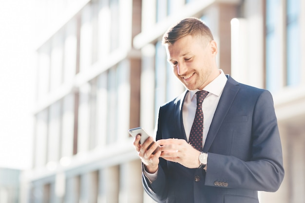 Young prosperous businessman chats online or reads information via cell phone