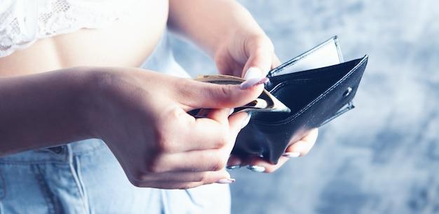 젊은 매춘부가 회색 배경에 있는 고객에게서 돈을 훔친다