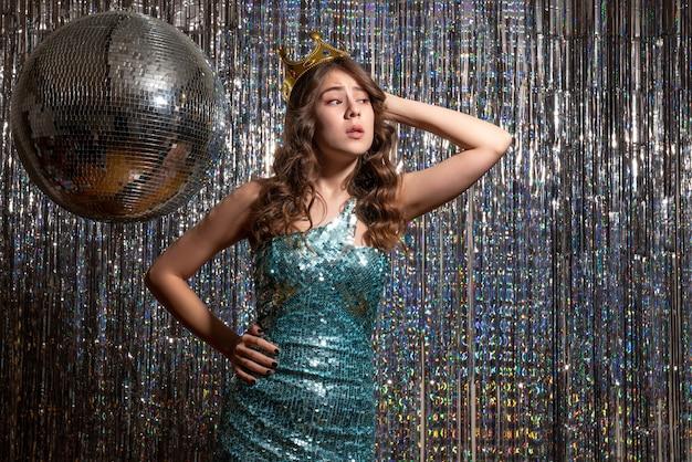 파티에서 왕관과 함께 장식 조각과 푸른 녹색 반짝이 드레스를 입고 젊은 자랑스런 매력적인 아가씨