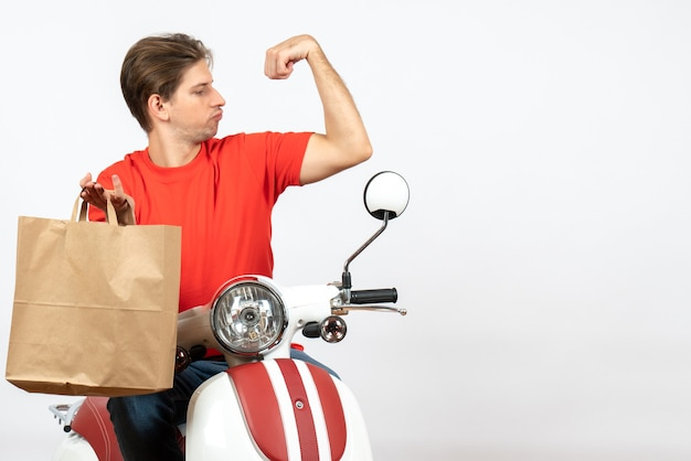 Young proud delivery guy in red uniform sitting on scooter holding paper bag and showing his muscular on white wall