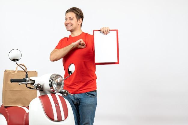 Giovane fattorino orgoglioso in uniforme rossa in piedi vicino a scooter che mostra il documento sul muro bianco