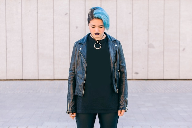 Young punk woman with blue dyed hair and a leather jacket looking down