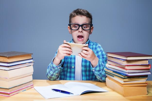 教室で彼の電話で遊んでメガネの若い生徒。タブレットpcの小さな少年