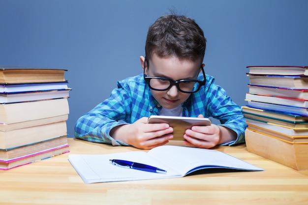 教室で彼の電話で遊ぶ若い生徒