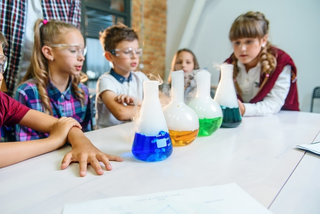 Young pupils watch the process of chemical reaction in colored liquids and dry ice in test flasks.