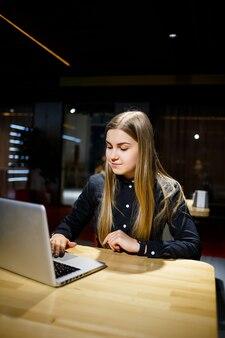 Молодая целеустремленная женщина, работающая над новым бизнес-проектом в офисе. одет в черную рубашку.