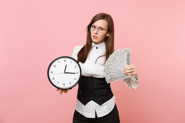 Young puzzled business woman in suit glasses holding bundle lots of dollars, cash money and alarm clock isolated on pink background. lady boss. achievement career wealth. copy space for advertisement.