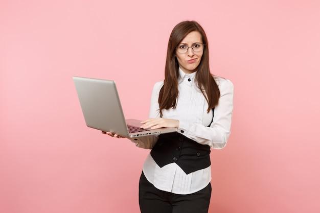 パステルピンクの背景で隔離のラップトップpcコンピューターで働くスーツと眼鏡の若い困惑した心配しているビジネス女性。女上司。達成キャリア富の概念。広告用のスペースをコピーします。