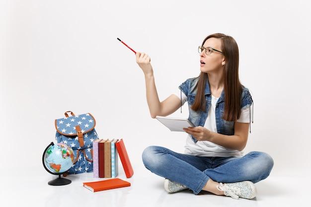 Молодая озадаченная обеспокоенная студентка в очках, указывая карандашом в сторону, держит ноутбук, сидя рядом с глобусом, рюкзак, школьные учебники, изолированные