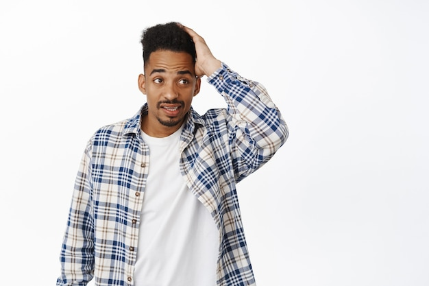 Young puzzled and confused african american guy dont know what to do, scratch head and look aside with questioned clueless face, dont understand whats happened on white