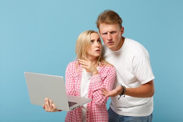 白いピンクの空白のtシャツのポーズで若い困惑したカップルの友人の男性と女性
