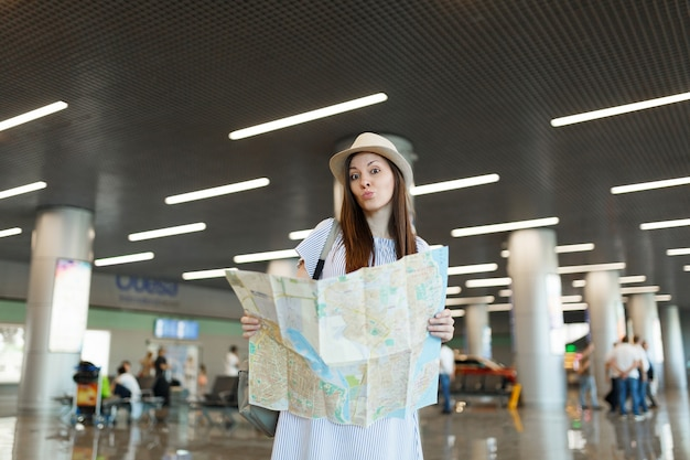 Young puzzled traveler tourist woman in hat holding paper map, searching route while waiting in lobby hall at international airport