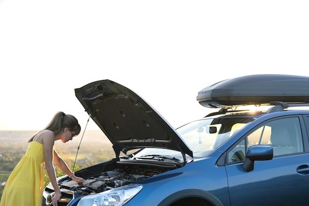 壊れたエンジンを見ているポップアップフードで彼女の車の近くに立っている若い困惑した女性ドライバー。