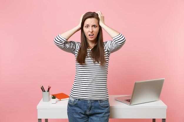 パステルピンクの背景に分離されたラップトップで白い机の近くに立って仕事、カジュアルな服を着た若い困惑した女性。業績ビジネスキャリアコンセプト。広告用のスペースをコピーします。