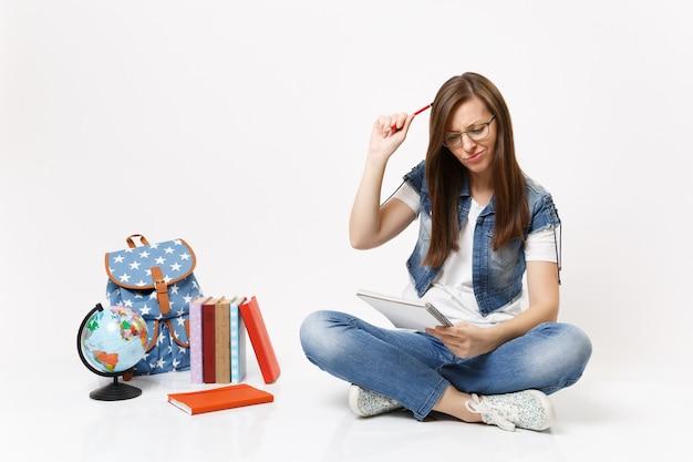 若い困惑した女性の学生は、白い壁に隔離された地球のバックパックの本の近くのノートブックを見て鉛筆で頭をスクラッチする方法を見つけると思います