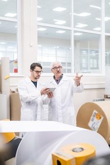 先輩と作業プロセスについて話し合っている間、機械のチェックにタブレットを使用している白衣の若い品質検査官