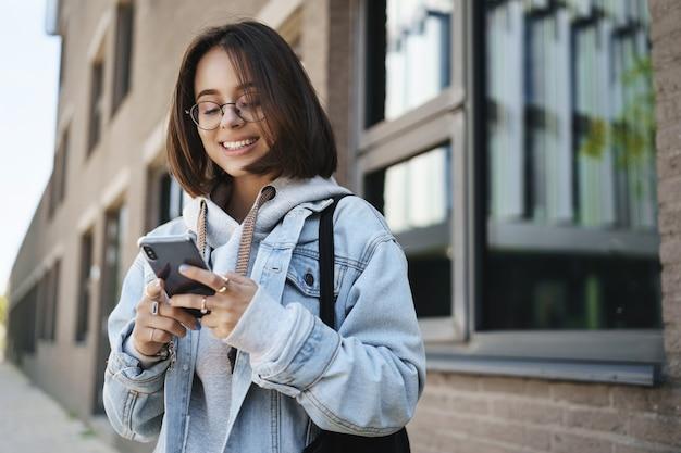 젊은 퀴어 소녀, 거리에 서있는 대학생, 스마트 폰에서 응용 프로그램을 사용하여 택시를 주문하고, 문자 메시지 친구로 웃고, 캠퍼스 밖에서 팀과 만나고, 소셜 미디어에서 뉴스 피드를 스크롤합니다.