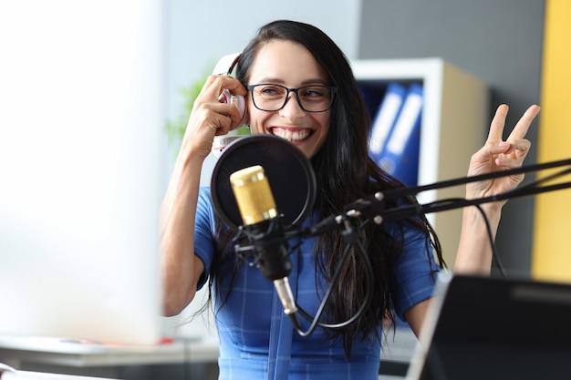 젊은 라디오 발표자는 스튜디오에서 일하며 미소를 지으며 라이브 라디오 발표를 방송합니다.