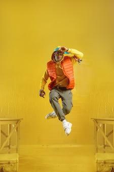 若いラッパーが黄色のトーンでスタジオにジャンプします。ヒップホップパフォーマー、ラップシンガー、ブレイクダンスパフォーマンス、エンターテインメントライフスタイル