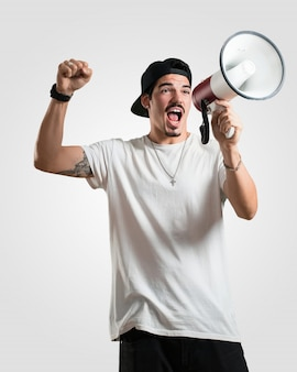 Young rapper man excited and euphoric, shouting with a megaphone, sign of revolution and change, encouraging other people to move, leader personality