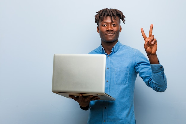 Молодой раста черный мужчина держит ноутбук, показывая номер два пальцами.
