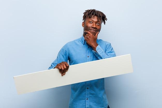 Молодой раста черный мужчина держит плакат, глядя в сторону с сомнительным и скептическим выражением лица.