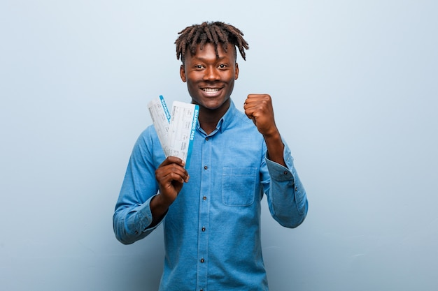 Young rasta black man holding an air tickets showing fist, aggressive facial expression.