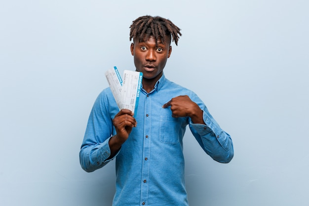 Young rasta black man holding an air tickets surprised pointing at himself, smiling broadly.