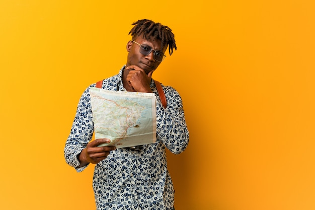Young rasta black man holding a map looking sideways with doubtful and skeptical expression.
