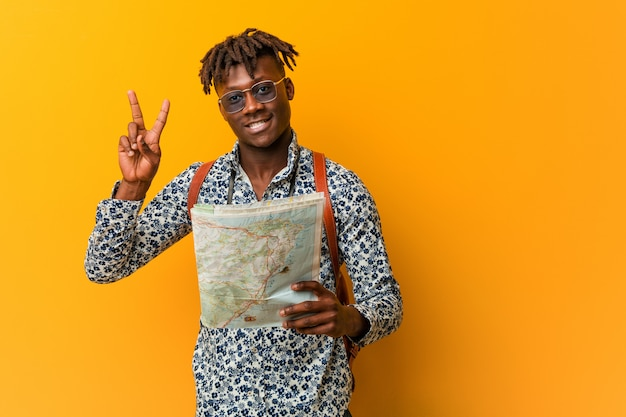 Young rasta black man holding a map showing victory sign and smiling broadly.