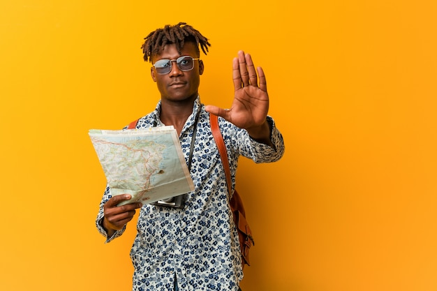 Young rasta black man holding a map standing with outstretched hand showing stop sign, preventing you.