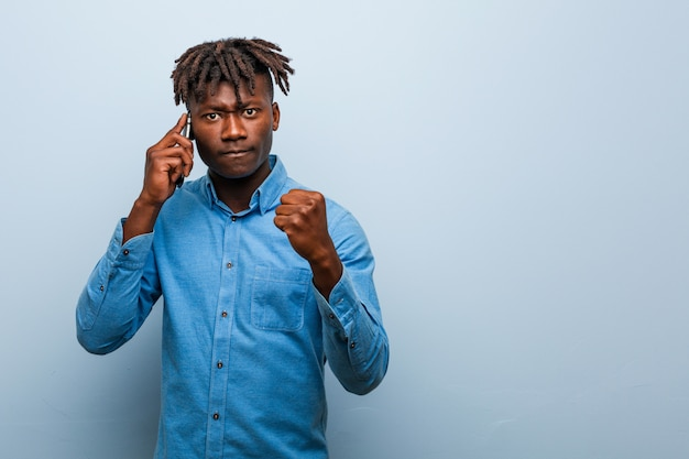 Young rasta black man holding a phone showing fist to camera, aggressive facial expression.