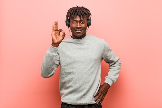 若いラスタ黒人男性が明るくて自信を持ってokのしぐさを示すヘッドフォンで音楽を聴きます。