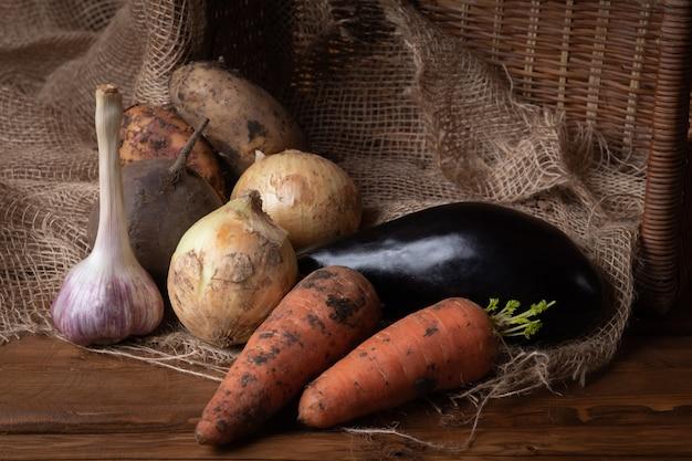 若い生の汚れたジャガイモ、玉ねぎ、ニンジン、ニンニク、ナスの木製の背景