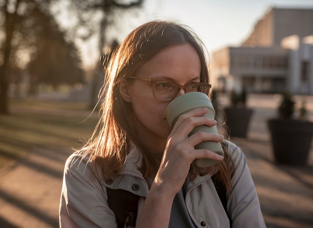 Молодая настоящая откровенная женщина в очках с многоразовой кофейной чашкой в руках, пьет кофе из эко-кружки с подсветкой.