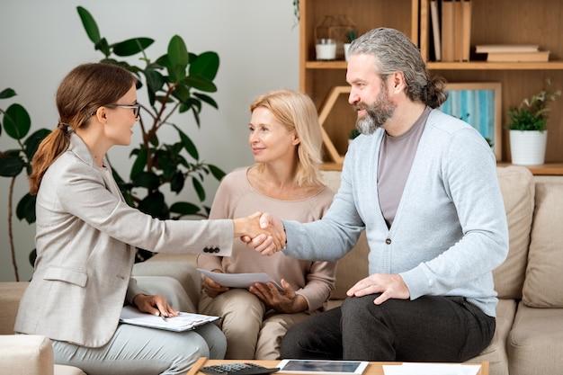 Молодой агент по недвижимости поздравляет зрелую пару с покупкой нового дома после подписания документов