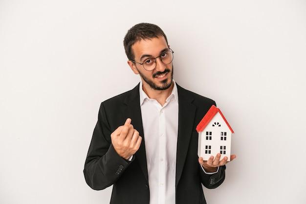 白い背景に隔離されたモデルハウスを持っている若い不動産業者の男が、誘うようにあなたに指を向けて近づいています。