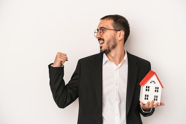 勝利、勝者のコンセプトの後に拳を上げる白い背景で隔離のモデルハウスを保持している若い不動産エージェントの男。