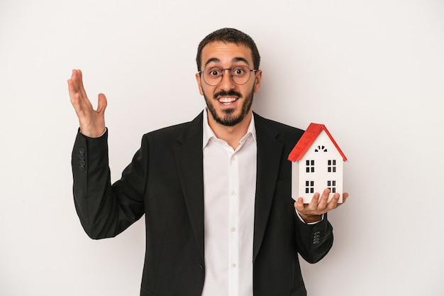 白い背景で隔離のモデルハウスを保持している若い不動産エージェントの男は、嬉しい驚きを受け取り、興奮し、手を上げます。