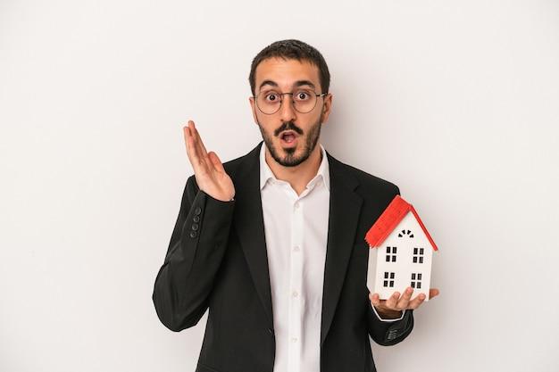 白い背景で隔離のモデルハウスを保持している若い不動産エージェントの男は驚いてショックを受けました。