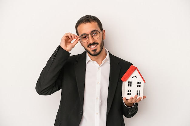Young real estate agent man holding a model house isolated on white background excited keeping ok gesture on eye.