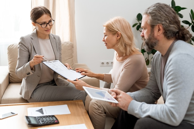 Young real estate agent with document pointing at sum of financial expenses while consulting mature couple at meeting